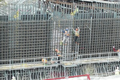 Workers do rebar work and form work for a Unit 2 wall in preparation for a concrete pour.