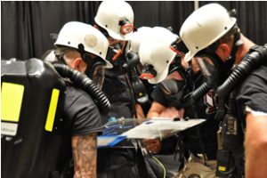 Rescue teams study mine map to locate trapped miners in simulated emergency drill