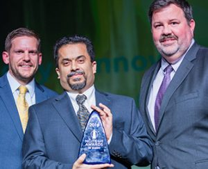 Martin Marietta vice president and chief information officer John Mohr (far right) and manager of business intelligence Ram Acharya (center) accept the award on behalf of the company. Presenter and NCTA board of advisors member Jason deFreitas appears at left